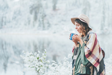 Young woman with cup in hands spending vacations among stunning winter landscape. Traveling in mountains wilderness. Wanderlust and boho style