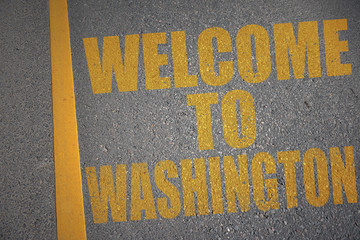 asphalt road with text welcome to washington near yellow line.