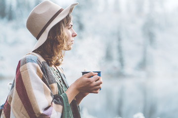 Pretty woman with hot drink in hands spending vacations among stunning winter landscape. Traveling in mountains wilderness. Wanderlust and boho style