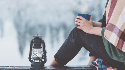Woman with cup of hot drink and kerosene lamp sitting near mountain lake and spending vacations among stunning winter landscape. Wanderlust and boho style. Close-up