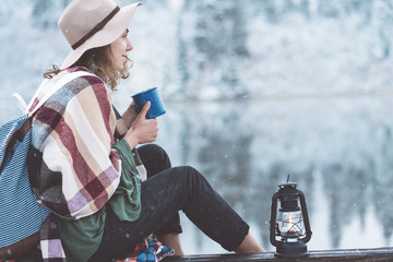 Stylish woman with cup of hot drink and kerosene lantern sitting near mountain lake and spending vacations among stunning winter landscape. Wanderlust and boho style