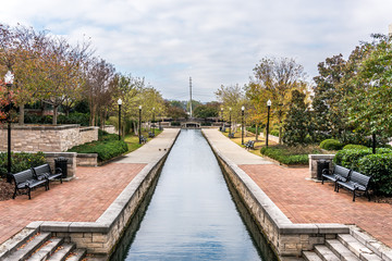Waterway in park with benches and concrete foreground