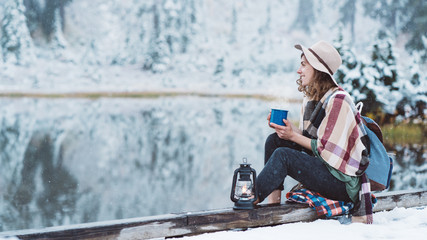 Smiling pretty woman with cup of hot drink and oil lamp sitting near mountain lake and spending vacations among stunning winter landscape. Wanderlust and boho style