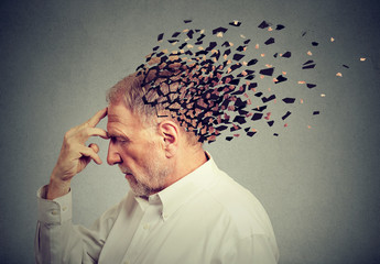 Memory loss due to dementia. Senior man losing parts of head  as symbol of decreased mind function. Wall mural