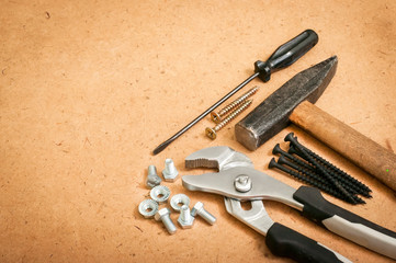 common tools, a hammer, a screwdriver, a wrench, a wrench and bolts, nuts, screws on a wooden background