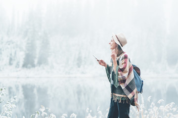 Handsome woman listening music using mobile phone outdoors. Traveling among stunning winter landscape. Vacations in mountain wilderness. Wanderlust and boho style