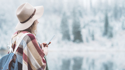 Stylish young woman with poncho and backpack using mobile phone in first snow. Traveling among stunning winter landscape. Vacations in mountain wilderness. Wanderlust and boho style