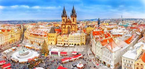 Prague in Christmas time. Winter snowy scenery. Classical panoramic view on old Town Square and Tyn church with Christmas fair market in Prague , Czech Republic. New Year festive time.