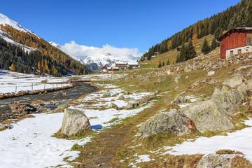 Dischmatal mit dem Dischmabach, einem Wanderweg und einigen großen Felsen Davos in Graubünden, Schweiz. Im Herbst nach Schneefall.