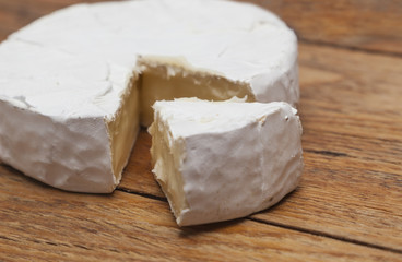 French Camembert cheese on rustic wooden background