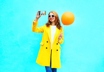 Fashion pretty woman takes a picture self portrait on a smartphone with an air balloon in yellow coat on blue background