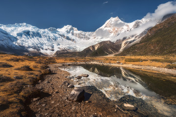 Wall Mural - Beautiful view with high rocks with snow covered peaks, stones in mountain lake, reflection in water, blue sky with clouds in sunrise. Nepal. Amazing landscape with Himalayan mountains. Himalayas