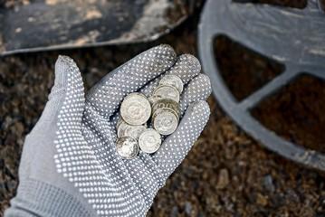 куча серебряных монет над катушкой металлоискателя