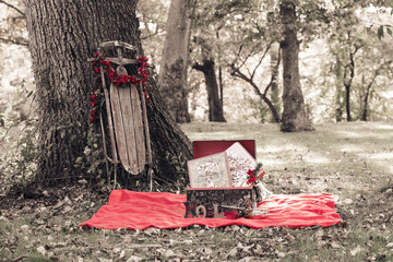 Vintage Christmas scene with vintage sled and gifts in nature setting for holiday backdrop
