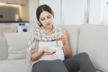Sick pregnant woman sitting at home on the couch. She's getting ready to drink a pill.
