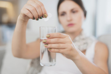 Sick pregnant woman sitting at home on the couch. She throws two tablets into a glass of water