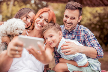 Smiling young family taking selfie in the park.