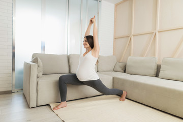 Pregnant sport. A pregnant woman sits on a light floor at home. She does yoga exercises
