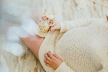 Pregnant girl in a knitted sweater beige color sitting on floor and holding a small cell