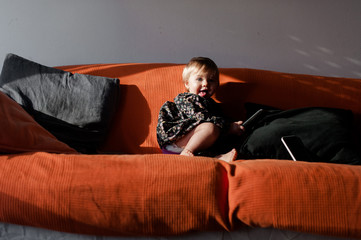girl on an orange couch with remote control