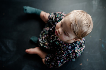 baby girl sitting on a blackboard