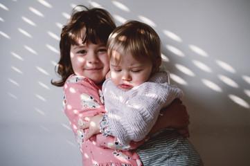 girl holding baby in the light