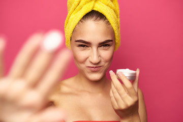 young girl with a yellow towel on her head holds a face cream
