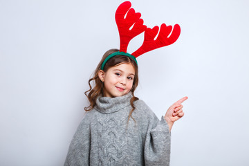 Happy little smiling girl showing product .Christmas concept. Smiling funny girl in deer horns in studio.