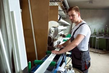 Worker in the workshop prepares pvc profiles