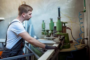 Worker operating welding machine in factory.