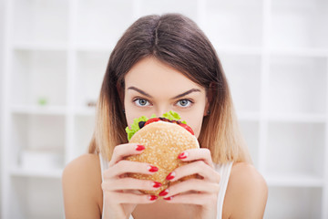 Diet. Young woman with duct tape over her mouth, preventing her to eat junk food. Healthy eating concept