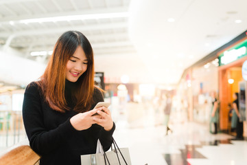 Portrait of beautiful young asian woman in shopping mall, smiling using smart phone to network indoors. Tourist woman using technology, travel lifestyle. Shopping mall exterior with clothing store.