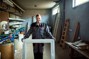 Worker in workshop for manufacture of windows and doors