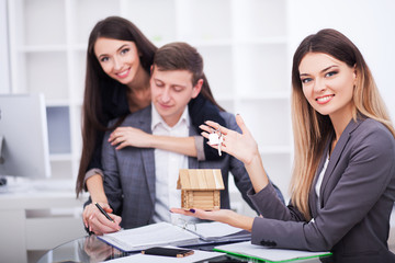 Meeting with agent in office, buying renting apartment or house, buyers of real estate ready to conclude a deal, family couple shaking hands with realtor after signing documents for realty purchase