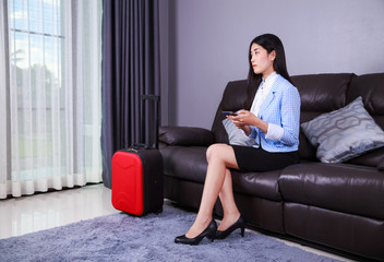 woman with suitcase and mobile phone sitting on sofa in home