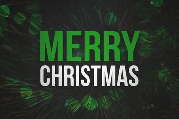 Merry Christmas Text with Pine Branches Background and Green Bokeh Lights