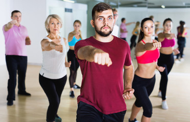 Men women performing modern dance in fitness studio