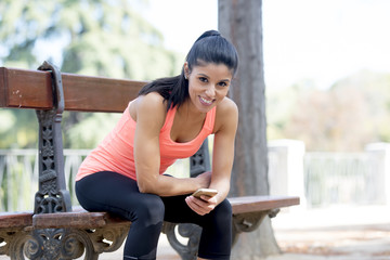 fit sport woman looking at mobile phone internet app tracking performance after running workout sitting on park bench happy