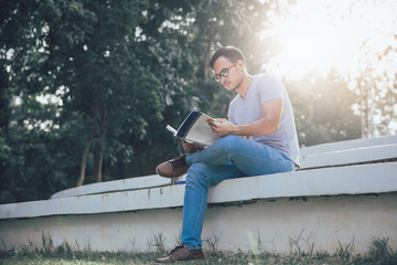 young asian student reading a book at the public park
