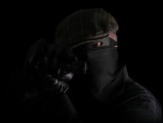 Masked robber holding gun sideways with leather gloves