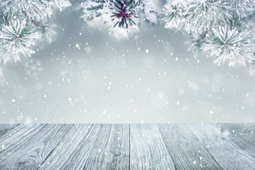 Winter background, falling snow on pine tree and wooden deck