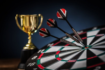 winning competition with red three darts arrows in the target center with golden trophy victory prize concept business ideas