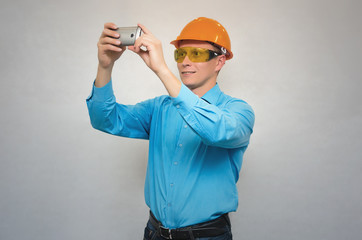 A builder worker holds a mobile phone in his hands and takes pictures of him and smiles isolated.