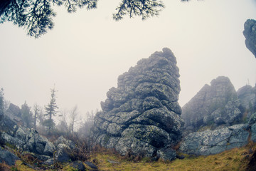 Dark mountain landscape with big mysterious rocks covered by fog