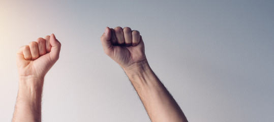 Clenched fists and arms raised in victorious manner