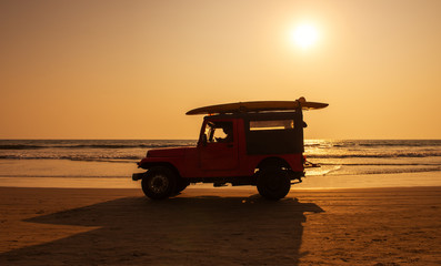 Surf rescue vehicle on beach at sunset