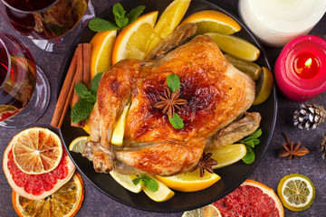 Chicken or turkey with lemons, oranges, limes and spices on Christmas and New Year background. Top view, horizontal