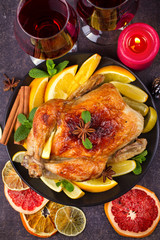 Chicken or turkey with lemons, oranges, limes and spices on Christmas and New Year background. Two glasses of wine. Top view, vertical