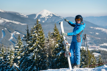 Shot of a female skier standing on top of a mountain with skis at winter resort, smiling, pointing at stunning natural landscape surrounding her copyspace enjoyment happiness recreation seasonal sport
