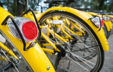 Close up Bicycle tail light on group of yellow vintage bike parking in the Park to service the touristi n bike sharing concept.